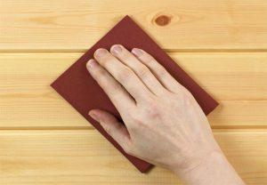 Chà nhám nhẹ bằng giấy nhám mịn trước khi đánh vecni đồ gỗ